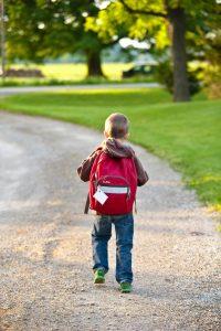 boy-in-brown-hoodie-carrying-red-backpack